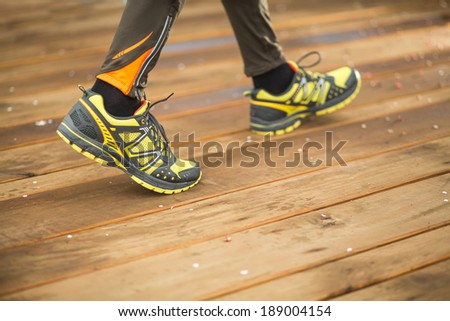 Feet of jogging man on wooden bridge. focus on right shoe