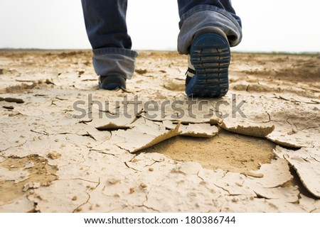 Feet of man walking through dry and cracked soil - stock photo