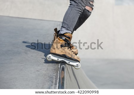 Feet of rollerblader wearing aggressive inline skates grinding on concrete ramp in outdoor skate park. Extreme sports athlete wearing roller blades for tricks and grinds - stock photo