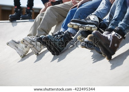 Feet of rollerbladers wearing aggressive inline skates sitting on concrete ramp in outdoor skatepark.Extreme sports athletes wearing roller blades for tricks and grinds.Skaters skating in skate park