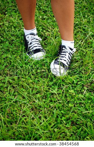 feet of the child of the teenager in gym shoes on a grass