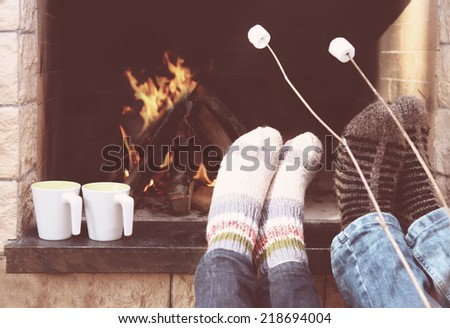 Feet of the couple warming at a fireplace with marshmallows on sticks - stock photo