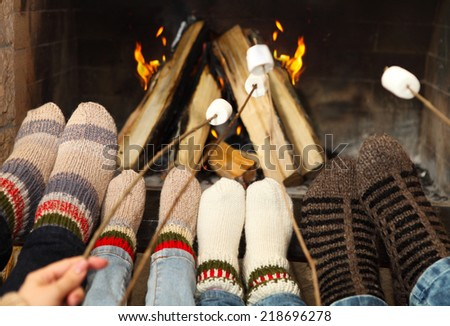 Feet of the family warming at a fireplace with marshmallows on sticks - stock photo