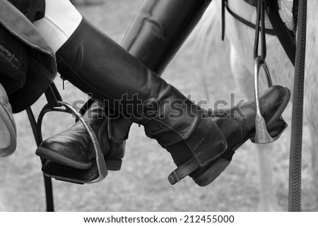 Feet of two pony friends putting their horse riding boots on each others stirrup. Image in black and white with focus on boots. - stock photo