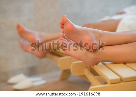 Feet of two women relaxing at beauty spa room - stock photo