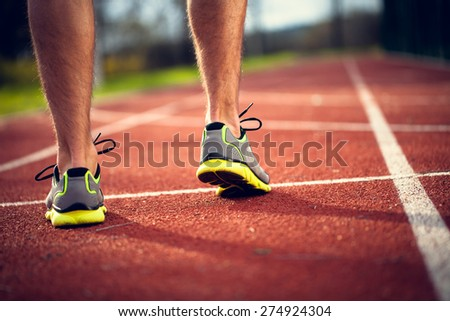 Feet of young athlete at the starting line ready to start - stock photo