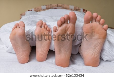 Feet of young couple in bed.