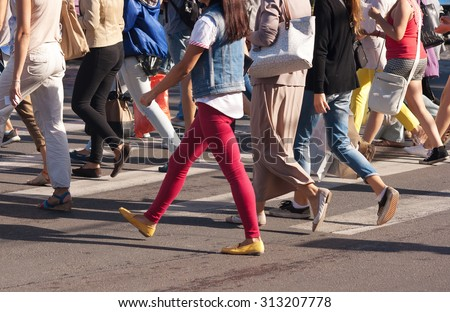 feet of young pedestrians walking on the crosswalk on summer day - stock photo