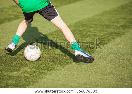 Feet of young players in soccer with a ball closeup. Junior league on soccer. Football game. Soccer game.