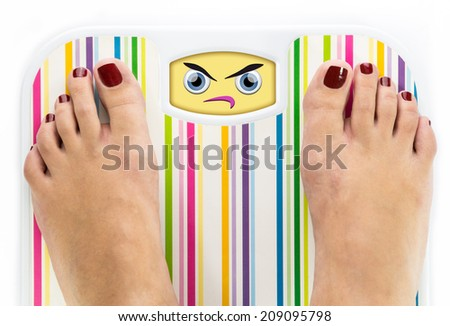 Feet on bathroom scale with angry cute face on dial - stock photo