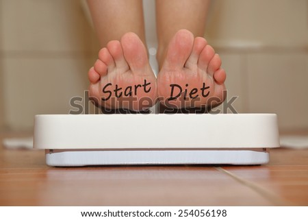 Feet on bathroom scale with hand drawn Start Diet text - stock photo