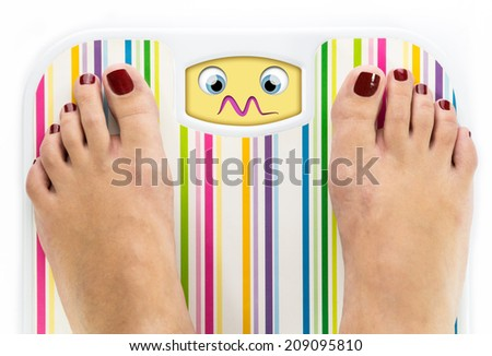 Feet on bathroom scale with overwhelmed cute face on dial - stock photo