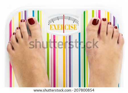"""Feet on bathroom scale with word """"Exercise"""" on dial - stock photo"""