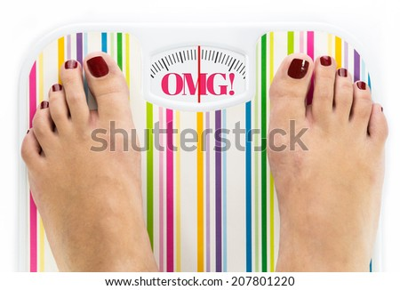 "Feet on bathroom scale with word ""OMG"" on dial - stock photo"