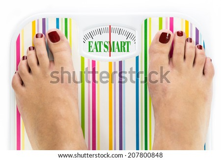 """Feet on bathroom scale with words """"Eat smart"""" on dial - stock photo"""