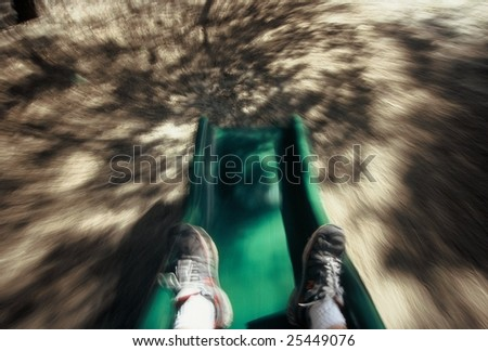 feet on green slide at playground