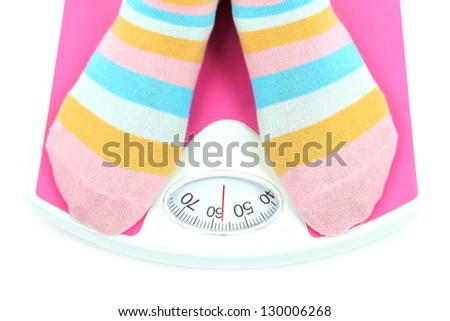 Feet on scales isolated on white - stock photo