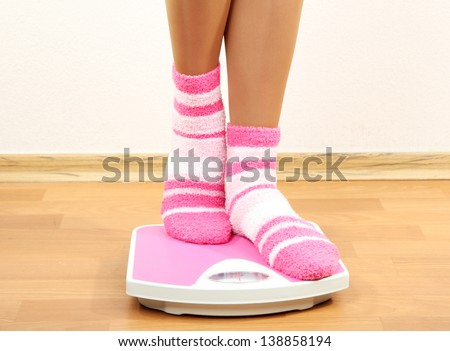 Feet on scales on floor in room - stock photo