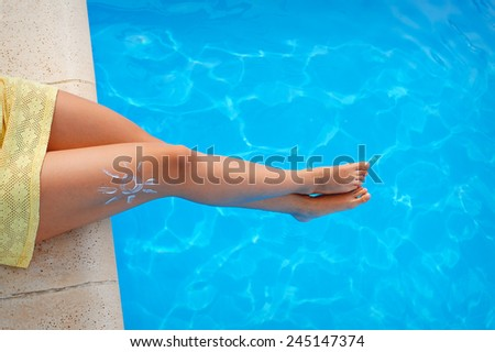 feet on the background of the pool with suntan lotion. - stock photo