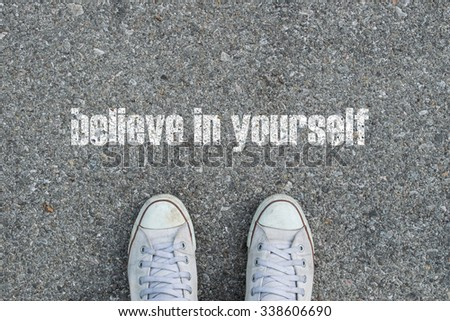Feet on the street and the message believe in yourself - stock photo