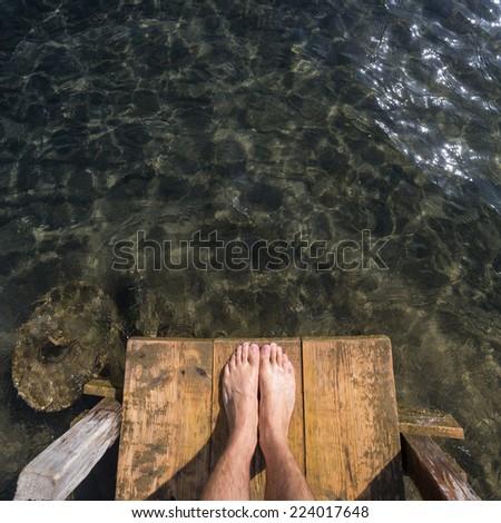 feet on wooden pier  - stock photo