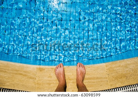 Feet overhanging by the side of a bright blue, crystal clear swimming pool
