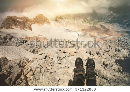 Feet selfie trekking boots on mountain summit outdoor Travel Lifestyle concept cloudy landscape on background Summer vacations journey aerial view - stock photo