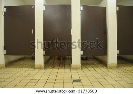 Feet Showing Under Bathroom Door In Public Restroom With Four Stalls