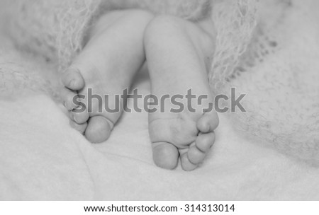Feet small baby on a white bed