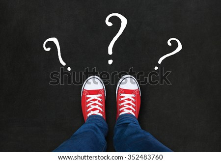 Feet wearing red shoes on black background with question marks. choice concept - stock photo