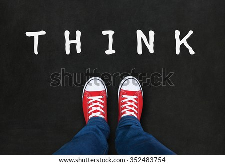 Feet wearing red shoes on black background with think word. choice concept - stock photo