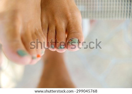 Feet with painted green toenails. - stock photo
