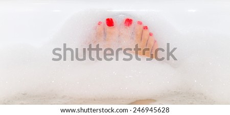 Feet with red nails soaking in spa bath with copy space - stock photo