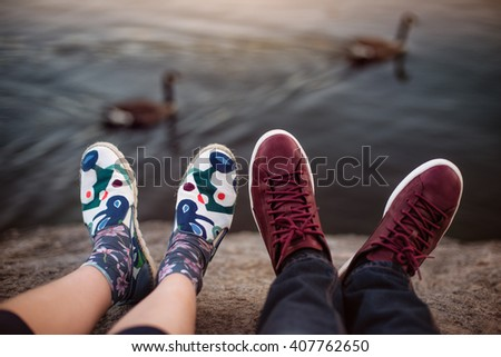 Feet with shoes of the couple on romantic date sitting on the rocks near lake - stock photo
