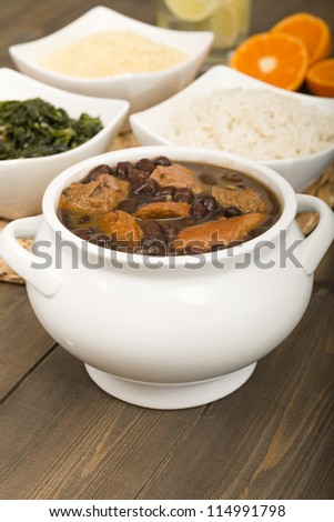 Feijoada - Brazilian beef, sausage, pork and black bean stew served with manioc flour, kale, white rice and oranges. Caipirinha on the background. Comfort Food! - stock photo