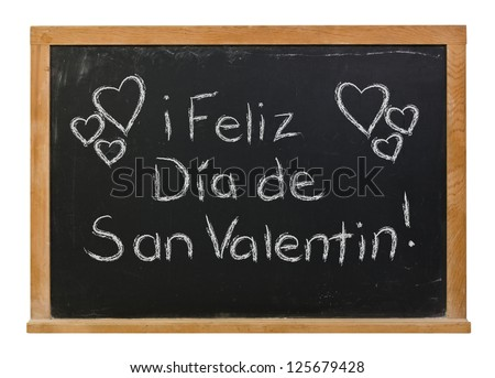 Feliz Dia de San Valentin or Happy Valentine's Day written in white chalk on a black chalkboard - stock photo