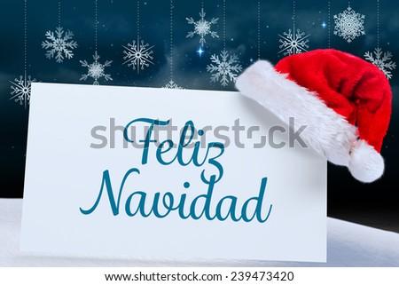 Feliz navidad against snowflake wallpaper over floor boards - stock photo