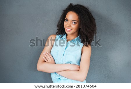 Felling carefree and relaxed. Portrait of attractive young African woman looking at camera and smiling while standing against grey background  - stock photo