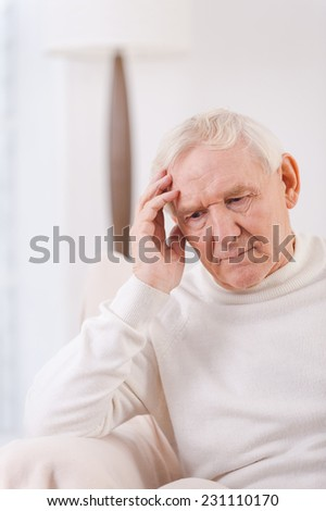 Felling lonely. Frustrated senior man touching his head while sitting in chair  - stock photo