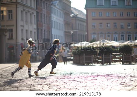 Fellow clowns running through the streets of the city, street theater concept - stock photo