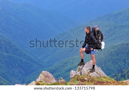 Fellow traveler with a backpack standing on a rock in the mountains - stock photo