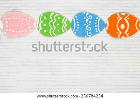 Felt Easter eggs on craft paper background - stock photo