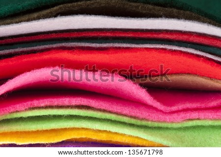 Felt fabric sheets in various colors piled up in a stack. - stock photo