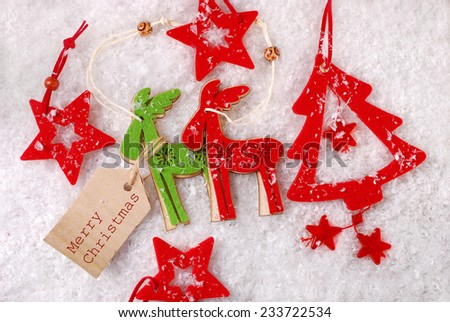 felt reindeer and star shape decorations lying on snow with paper tag for greetings - stock photo