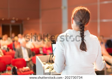Female academic professor lecturing at Conference. Audience at the lecture hall. - stock photo