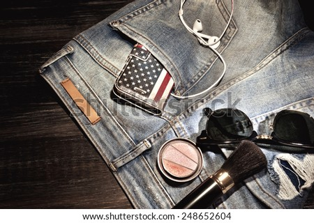 Female accessories and dirty jeans with cellphone in the pocket lying on floor - stock photo