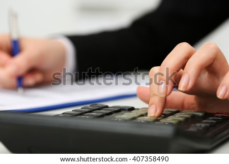Female accountant hand holding pen counting on calculator income for tax form completion closeup. Internal Revenue Service inspector checking financial document. Planning budget, audit concept - stock photo
