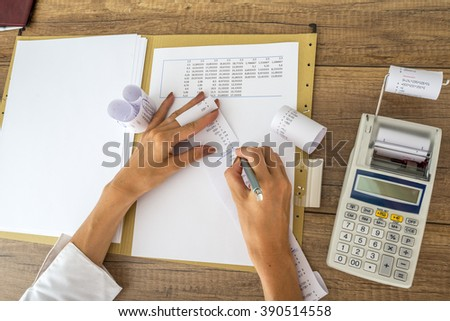 Female accountant or tax adviser working with receipts and statistical  data with calculator on her office desk. - stock photo