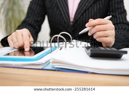 female accountant using assistance on tablet pc to complete work - stock photo