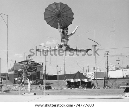 Female acrobat doing splits on tightrope - stock photo